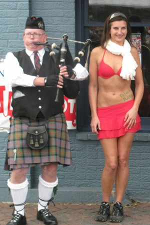 Miss Claus and a bagpiper at the Santa Speedo Run In Annapolis