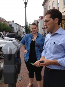 Mayor Cohen shows Maggie Lear how to use the new parking meters and pays for her parking with his credit card.