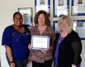 Katherine Gravelle, center, owner of the local Griswold Home Care franchise in Severna Park, presents a $1,000 check to Partners In Care's CEO Barbara Huston, right, and Member Care Coordinator Ashley Johnson, left.