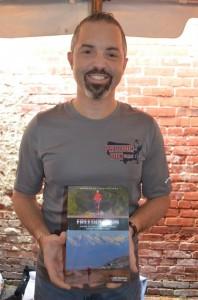 Jamie Summerlin displays his book, Freedom Run, at the Santa Speedo Run on Saturday. (Photo: Lisa Seborowski)