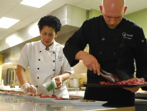 Roundz Gourmet owner Chef Zachary Pope and associate Chef Susan Moncrieffe prepare plates for diners on the exhibition kitchen counter.