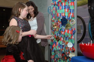 """Cape St. Claire Elementary fifth grader Makenzie Barrett selects her medal as little sister and Meghan Siegel, AAMC child life specialist, watch. Makenzie selected a medal featuring a guitar because she said, """"I love music. I love to sing. This makes me feel so special."""""""