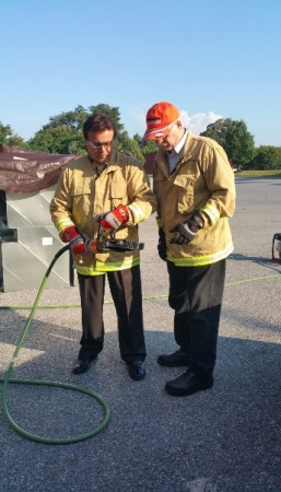 Photo by Francis X. Dunigan, Jr.; Holmatro Training Manager Al Sergio (Right) instructs Business Ombudsman Roger Campos on extrication techniques using Holmatro rescue tools.