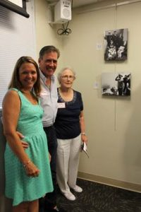 The family of Tribute Wall honoree Donald Green pose by his photo, which is marked as number 10 on the wall. They are, pictured from left, Mary, Mike and Betty Green.